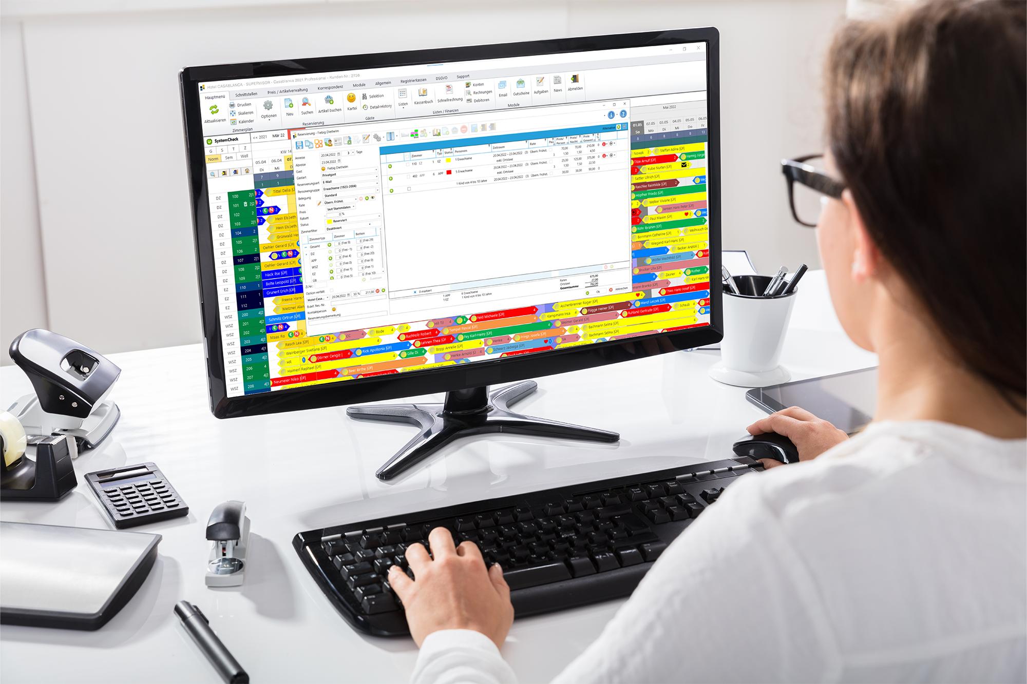 Frau arbeitet am Computer mit Casablanca Hotelsoftware
